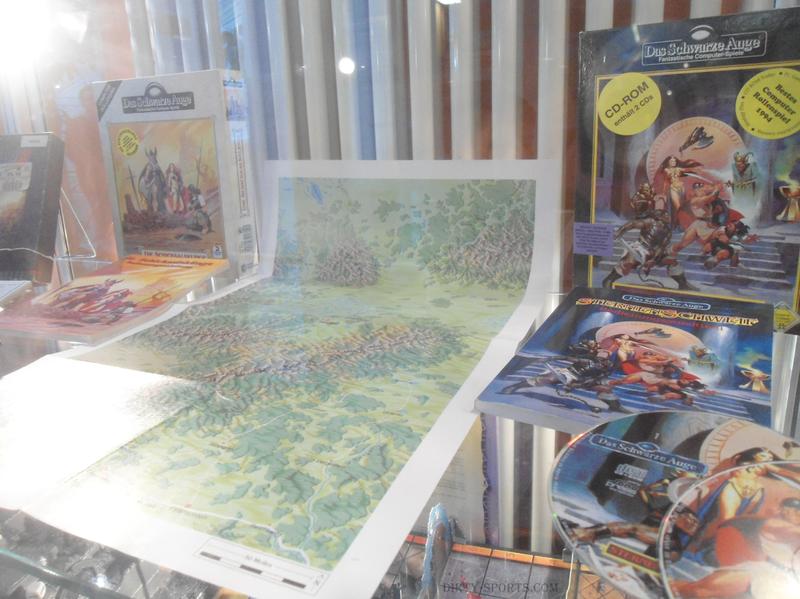 Lange Nacht der Computerspiele: Vitrine mit den Computerspieleboxen von Das Schwarze Auge. Zentral liegt die beiliegende Karte eines Teils von Aventurien. Daneben liegen Handbücher und CD´s der Spiele.