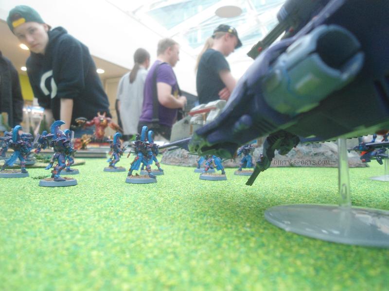 Lange Nacht der Computerspiele: Auf einem grün profilierten Bord wird das Tabletop-Spiel Warhammer gespielt. Man sieht aufwändig bemalte Figuren in Mini-Kampf-Szenarien.