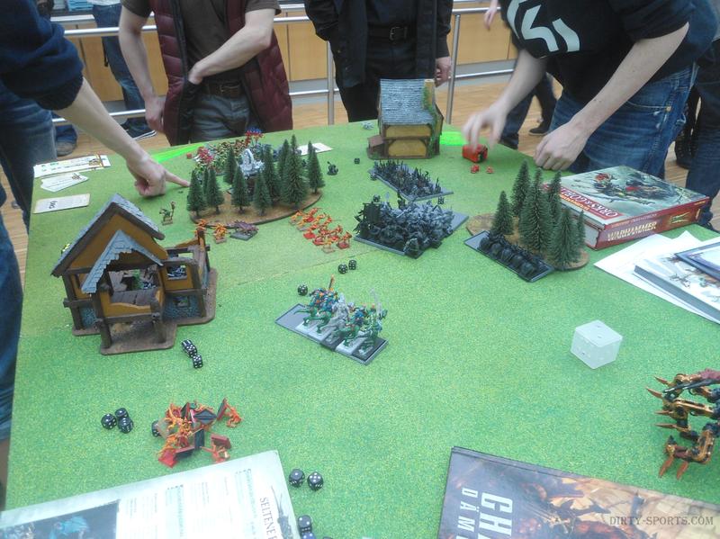 Lange Nacht der Computerspiele: Warhammer Figuren und Gebäude zum Kampf aufgestellt. ringsum liegen am Tisch Regelwerk, Messwerkzeuge und Würfel.