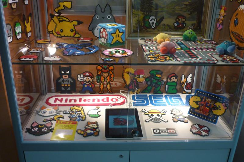 Lange Nacht der Computerspiele: Vitrine mit Bügelperlen-Objekten. Dargestellt viele klassische Videospiel Figuren.